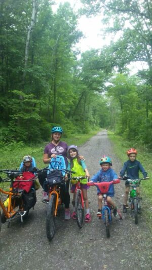 family in forest on bike
