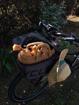 Black bike with straw basket in front bag.